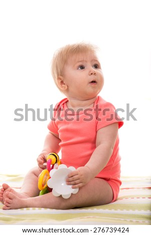 Blond baby girl sitting on blanket and looking away - stock photo