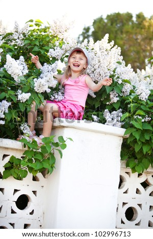 Blond baby girl sitting on fence at lilac, singing song and swinging arms