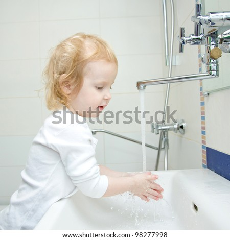 blond baby girl washing hands and face in the morning in the bathroom. The girl wearing a blank white shirt. Ready for your design or logo