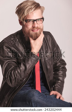 Blond beard fashion man sitting while fixing his beard with the right hand. He is smiling at the camera. - stock photo
