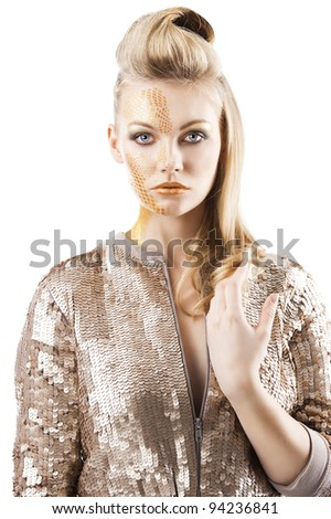 Blond beautiful creature with sequin jacket and creative make up making and hair stylish. She is in front of the camera, looks in to the lens and her left hand is near the chest. - stock photo