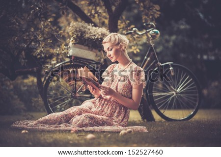 Blond beautiful retro woman reading book on a meadow  - stock photo