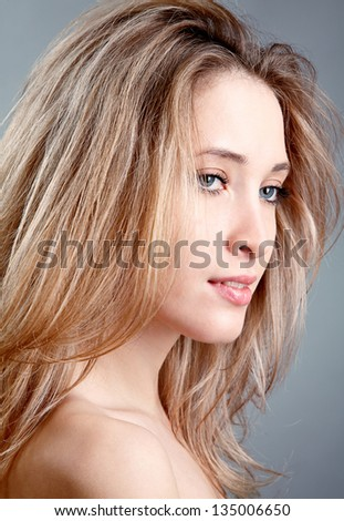 Blond beautiful woman over grey background - stock photo