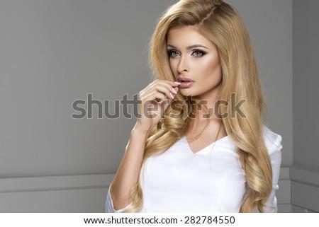 Blond beauty wearing white dress  - stock photo
