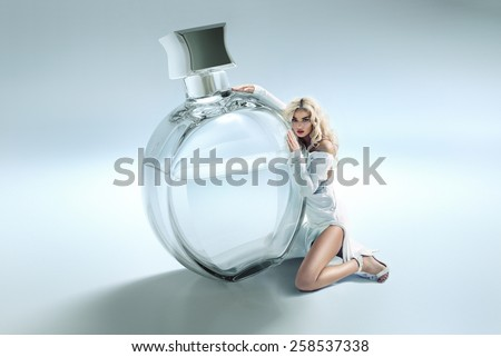 Blond beauty with a phial of perfume - stock photo