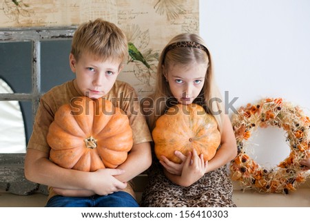 blond boy and girl studio portrait with pumpkins