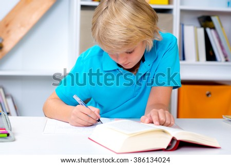 blond boy doing homework in his room