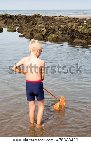 Blond boy fishing with net in a rock pool