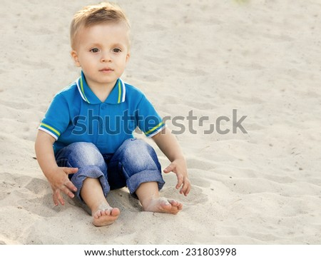 blond boy in a blue dress sitting on sand and looking to the side