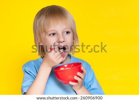 Blond boy kid child eating corn flakes cereal - stock photo