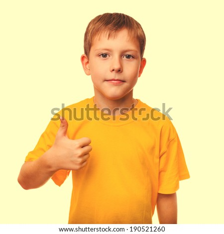 blond boy kid in a yellow shirt holding a thumbs-up, showing the sign yes on a white background cross processing retro