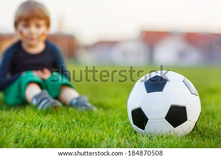 Blond boy of 4 playing soccer with football on football field, outdoors. Selective focus on ball.