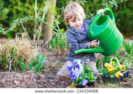 Blond boy of 2 years having fun with gardening and planting vegetable plants and flowers in garden, outdoors - stock photo