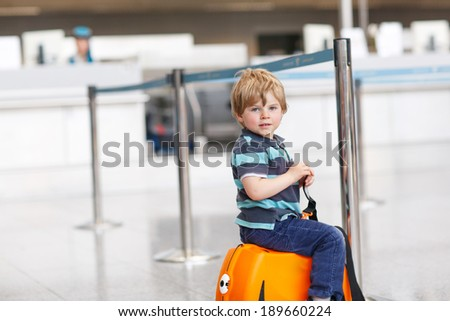 Blond boy of 2 years sitting on suitcase at the airport, indoors and waiting for going on vacations.