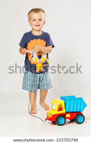 Blond Boy playing with the small plastic  car