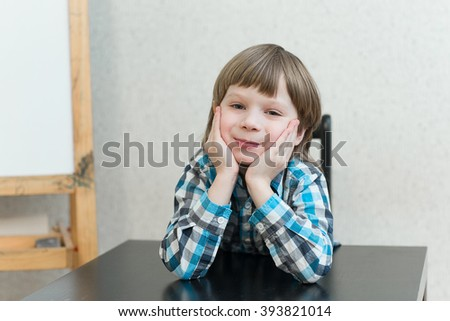 Blond boy sitting at the table at home and learns. The idea of school, home education and developmental activities. - stock photo