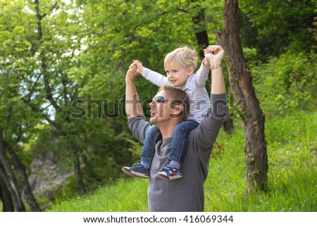 Blond boy sitting on fathers shoulder outdoors - stock photo