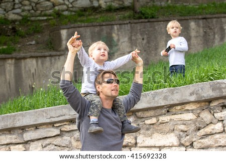 Blond boy sitting on fathers shoulder outdoors with 2nd son on background - stock photo