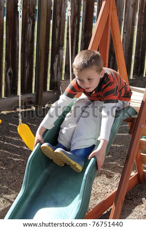 Blond boy sliding down a green slide