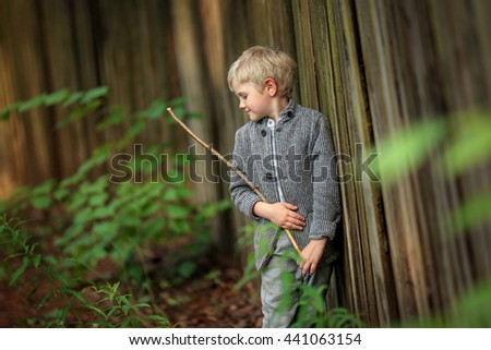 blond boy wearing a jacket standing near the fence and holding a stick in his hands - stock photo