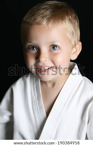 Blond boy with blue eyes in karate uniform - stock photo
