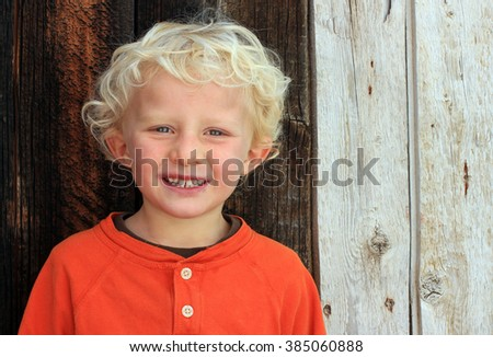 Blond boy with curly hair and a barn wood background. - stock photo