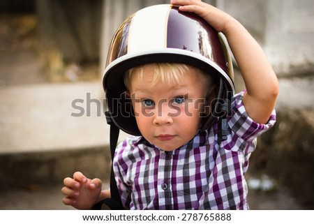 Blond boy with motorbike helmet, safety concept - stock photo