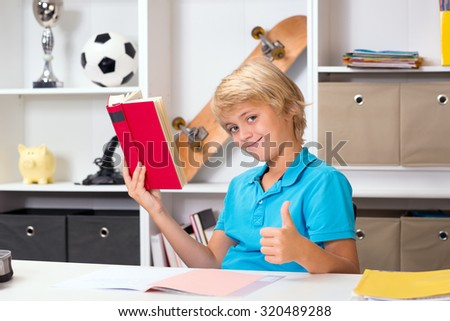 blond boy with thumb up doing homework and reading a book - stock photo