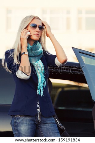 Blond business woman calling on the phone at the car - stock photo