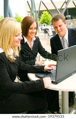 blond business woman pointing at laptop screen to her two associates