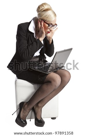 Blond business woman sitting and watching in astonishment at the laptop screen - stock photo