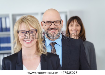 Blond business woman stands at head of line besides other people in suit jackets near shelf with binders - stock photo