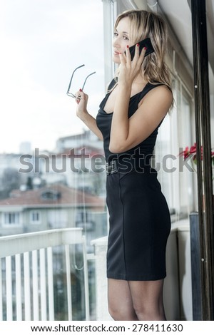 blond business woman talking on her cellphone standing next to the window - stock photo