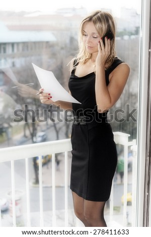 blond business woman talking on her cellphone standing next to the window