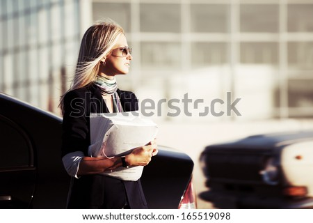 Blond business woman with financial papers - stock photo