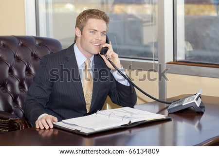 Blond businessman at work talking to the phone.