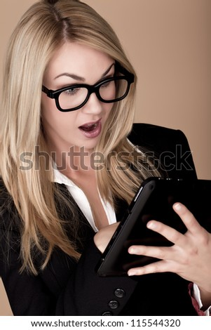 Blond businesswoman. A attractive blond businesswoman holding a black tablet computer. - stock photo
