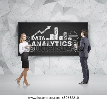 Blond businesswoman and her colleague are holding their coffee cups and looking at graphs and an analytics sketch drawn on a blackboard in room with triangular pattern background.