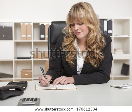 Blond businesswoman writing notes at her desk as she sits in her office with shelving lined with binders behind her - stock photo
