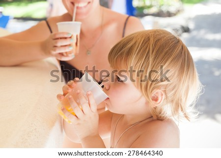 Blond Caucasian baby girl with young mother drink orange juice in an open resort bar - stock photo