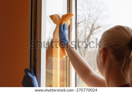 Blond Caucasian girl cleaning window inside her room in spring time - stock photo