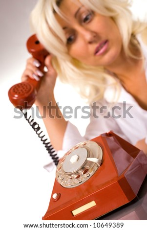 Blond caucasian model with red phone over white - stock photo