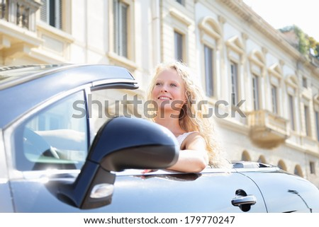 Blond Caucasian woman alone driving car on road trip freedom enjoying carefree holidays in summer vacation. Female driver in new car convertible smiling happy. Beautiful young woman in her 20s.