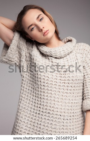 Blond cheerful young pretty woman. Beauty portrait, perfect makeup. Long chic elegant hair. Model tests. Cute girl in white sweater. Isolated. Gray background. - stock photo