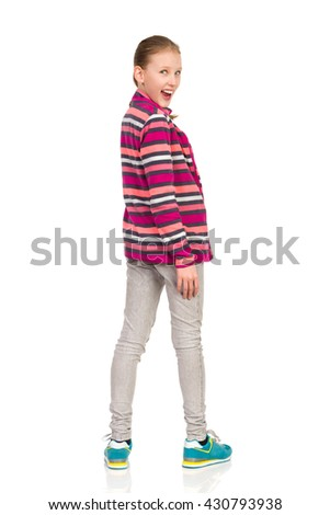 Blond child girl in striped fleece blouse, jeans and sneakers standing, looking over her shoulder and shouting. Rear view. Full length studio shot isolated on white.