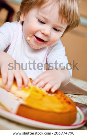 Blond crafty toddler boy eating cheesecake with his hands - stock photo