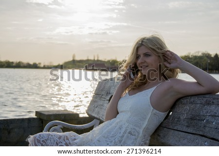 Blond curly woman sitting on a wooden bench and talking on the phone by the lake.