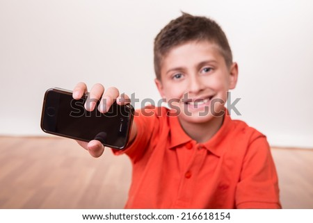 Blond cute boy holding his own cellphone - stock photo