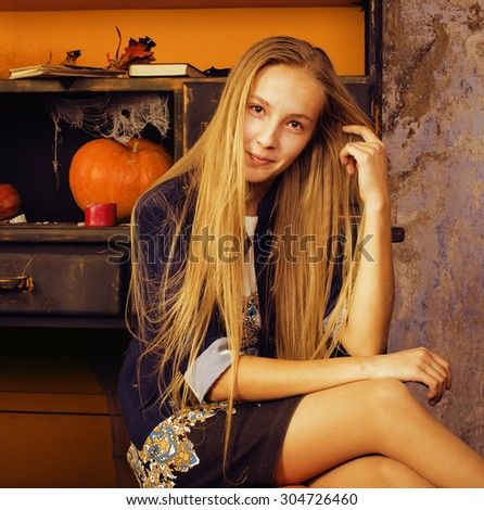 blond cute girl in halloween interior with pumpkin smiling - stock photo
