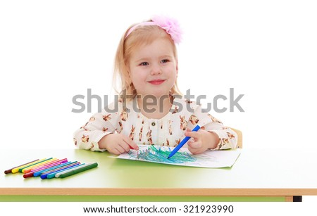 Blond cute little girl draws with markers at the table. On the head the girl has a big pink bow-Isolated on white background - stock photo